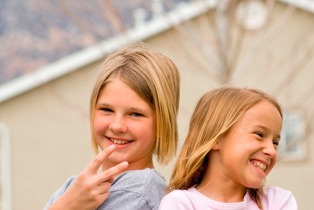 Meisjes (8-11) gebaren met huis op achtergrond, glimlachen, portret
