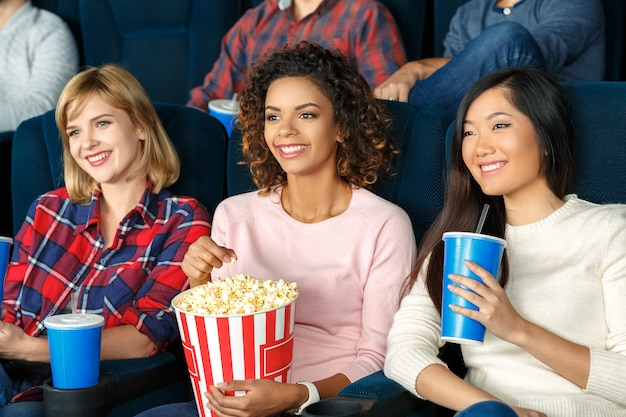 Meisjes avondje uit. mooie jonge meisjes die popcorn eten en samen een film kijken