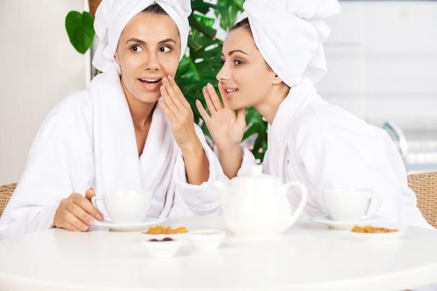 Meisjes bij kuuroord. twee mooie jonge vrouwen in badjas die thee drinken en roddelen terwijl ze voor het zwembad zitten