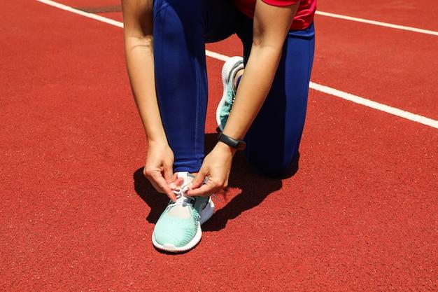 Meisjes bindende schoenveters op rode atletische renbaan, ruimte voor tekst