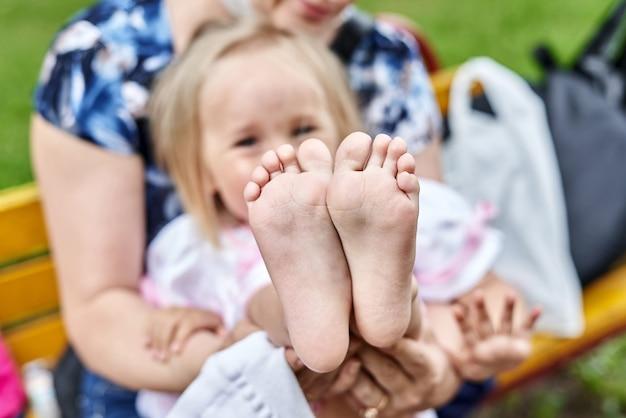 Meisjes blote voeten close-up. moeder verwisselt schoenen voor het kind