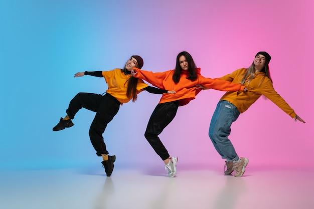 Meisjes dansen hip-hop in stijlvolle kleding op gradiënt studio achtergrond in neonlicht.