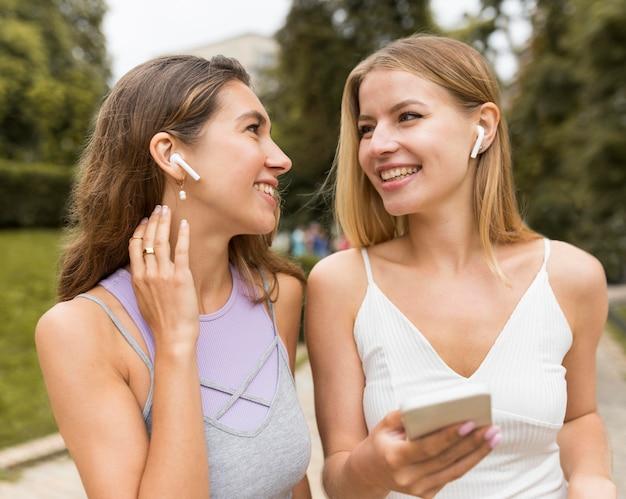 Meisjes die airpods in het park dragen
