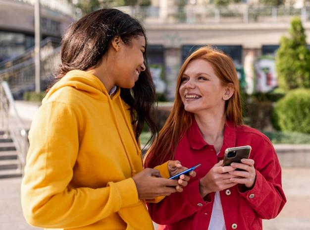 Meisjes die buitenshuis hun telefoons controleren