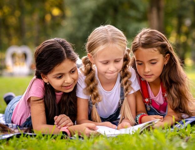 Meisjes die een boek op het gras lezen