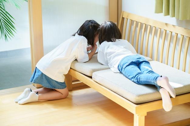 Meisjes die een geheim verhaal vertellen in een hoek van de kamer