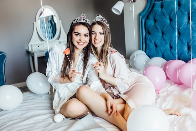 Meisjes die een luchtkus sturen, naar voren kijkend met vrijgezellenfeest thuis met ballonnen