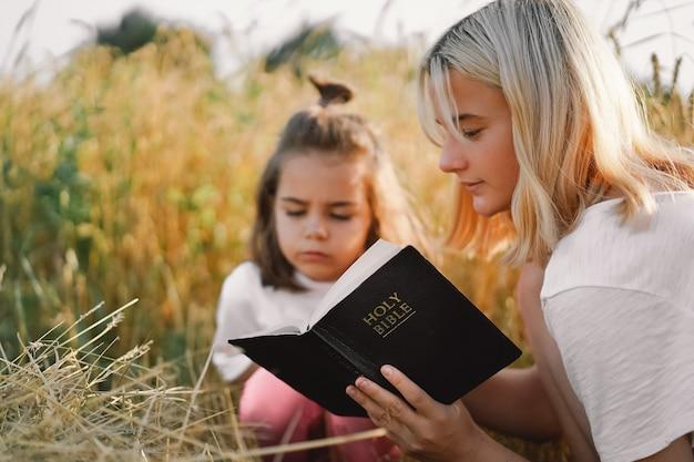 Meisjes die heilige bijbel in een tarweveld lezen. bestudeer samen de bijbel.