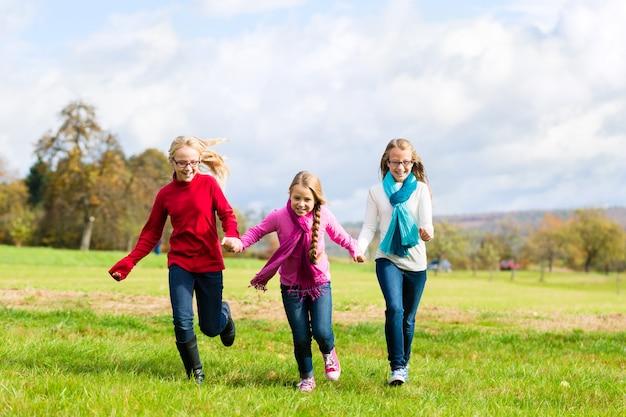 Meisjes die herfst of de herfstpark doornemen