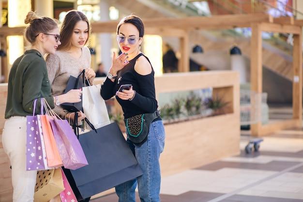 Meisjes die het winkelen zakken houden, asmart telefoon gebruiken en terwijl status glimlachen