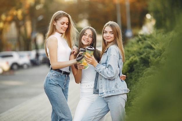 Meisjes die in een de lentestad lopen en koffie nemen