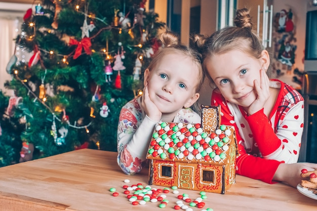 Meisjes die kerstmis peperkoekhuis maken bij open haard in verfraaide woonkamer.