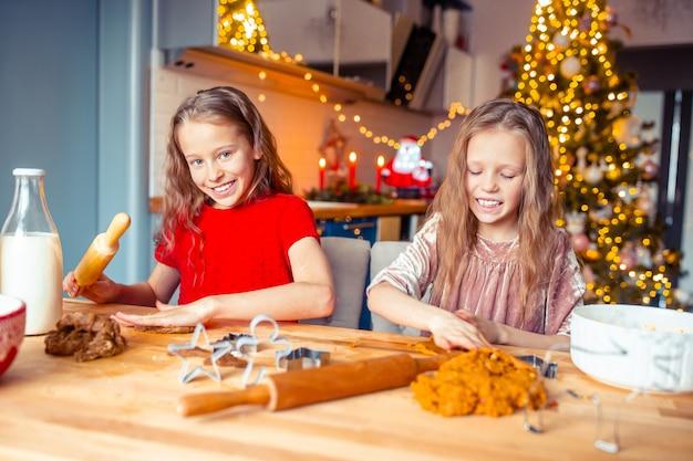 Meisjes die kerstmispeperkoekhuis maken bij open haard in verfraaide woonkamer.