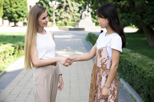 Meisjes die met de hand schudden en naar elkaar kijken