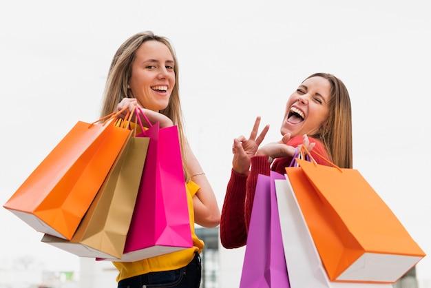 Meisjes die met het winkelen zakken camera bekijken