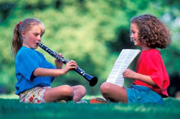 Meisjes die muziek op gras uitoefenen