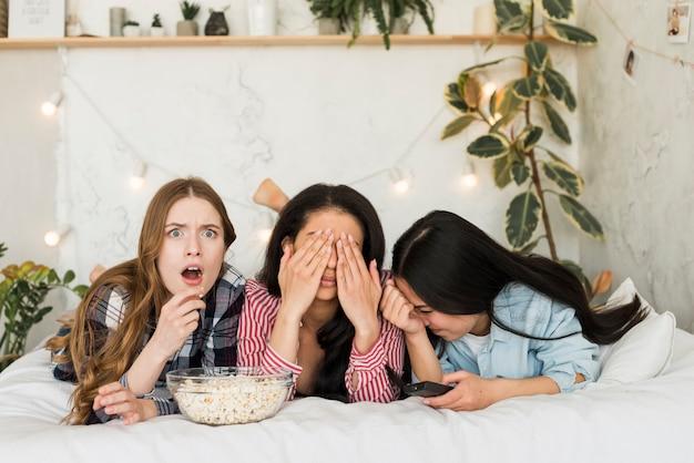Meisjes die op bed liggen en popcorn eten en pret hebben
