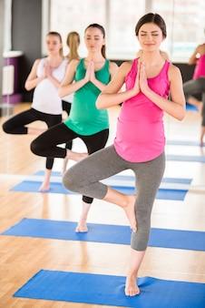 Meisjes die op één been staan, oefenen een oefening uit.