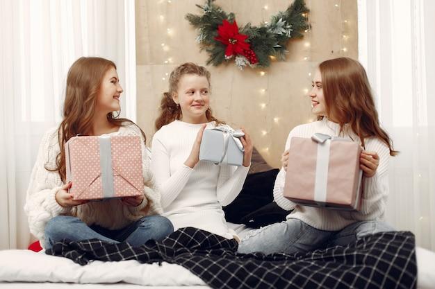 Meisjes die op het bed zitten. vrouwen met geschenkdozen. vrienden die zich voorbereiden op kerstmis.