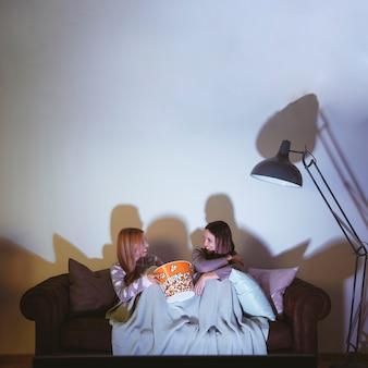 Meisjes die popcorn eten en een filmavond hebben