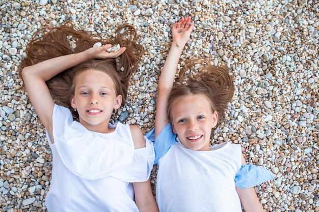 Meisjes die pret hebben bij tropisch strand tijdens de zomervakantie