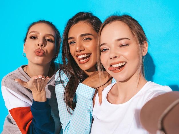 Meisjes die selfie zelfportretfoto's op smartphone nemen modellen die dichtbij blauwe muur in studio stellen.