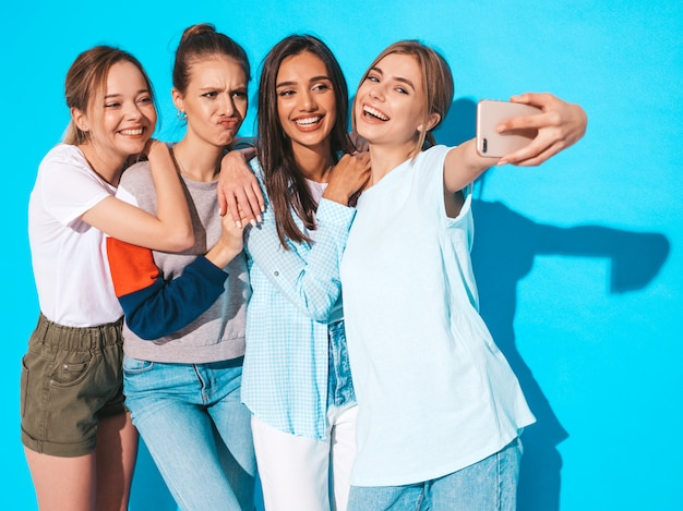Meisjes die selfie zelfportretfoto's op smartphone nemen modellen die dichtbij blauwe muur in studio, wijfje stellen die positieve gezichtsemoties tonen