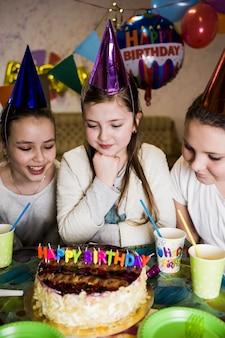 Meisjes die smakelijke cake bekijken