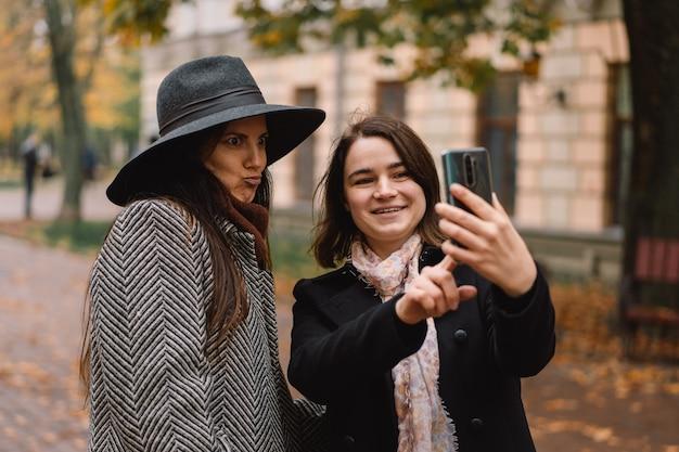 Meisjes die telefoon gebruiken voor videogesprek met vrienden in het park