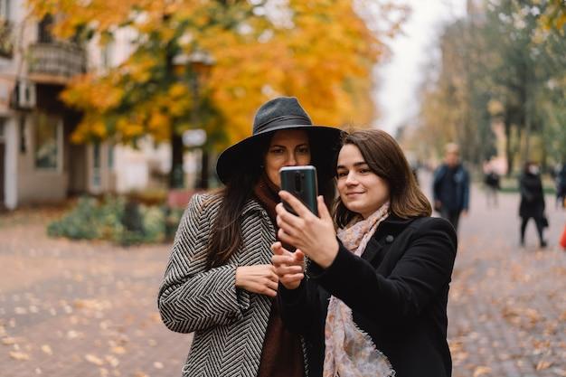 Meisjes die telefoon in het park gebruiken