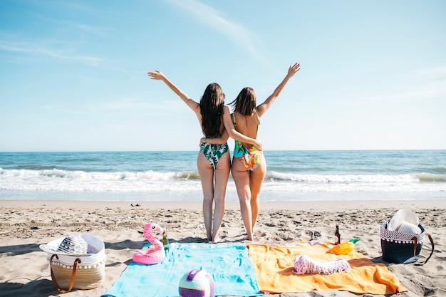 Meisjes die wapens opheffen op het strand