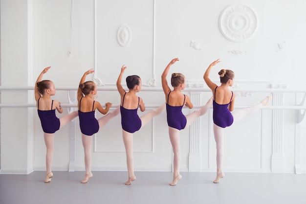 Meisjes die zich uitstrekken in de choreografie klas