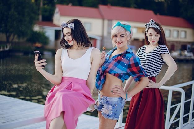 Meisjes die zich voordeed op een witte balustrade en te kijken naar haar mobiele telefoon