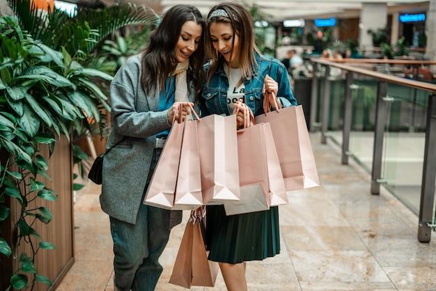 Meisjes doen aankopen in een winkelcentrum, gaan winkelen.