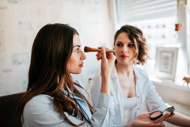Meisjes doen make-up in appartement.