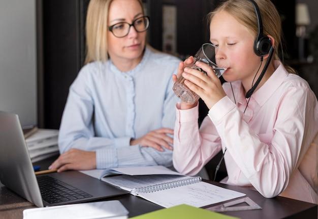 Meisjes drinkwater naast leraar