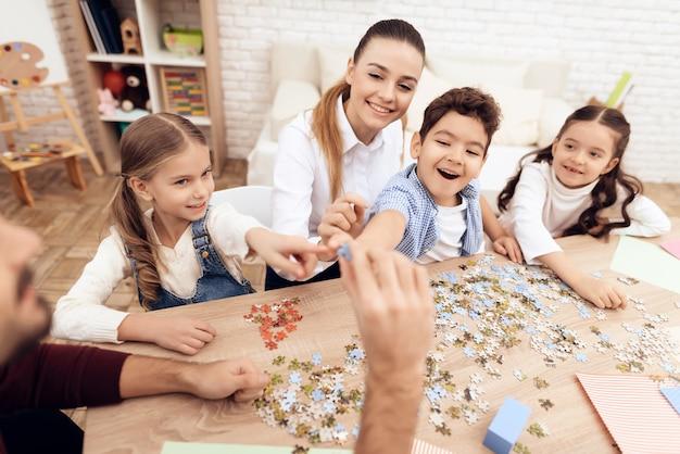 Meisjes en jongen in de klas shows op juiste puzzel.
