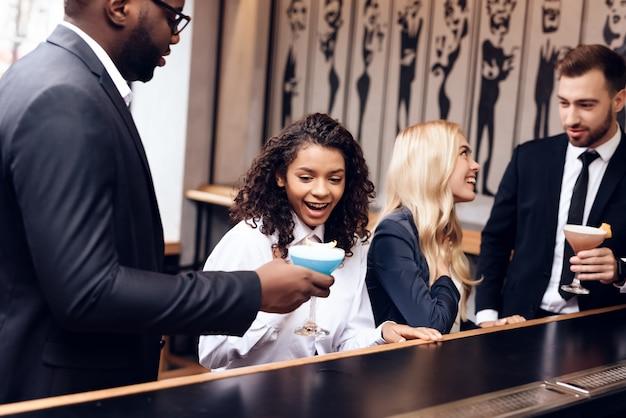 Meisjes en jongens communiceren elkaar in een bar.