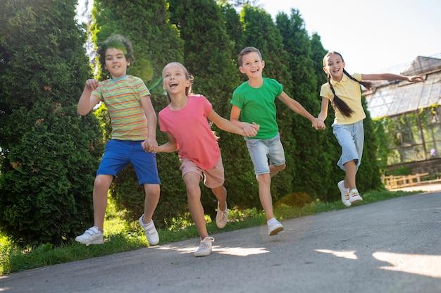 Meisjes en jongens springen hand in hand