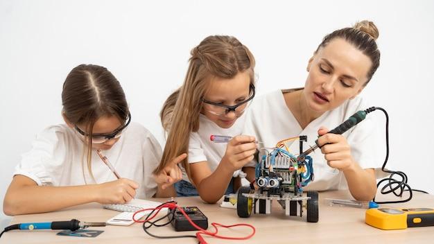 Meisjes en vrouwelijke leraar doen wetenschappelijke experimenten samen met robotachtige auto