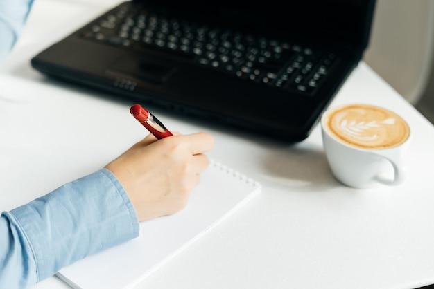Meisjes freelancer in een blauw shirt schrijft in een notitieboekje, op het bureau staat een zwarte laptop en koffie