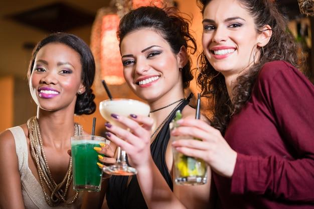 Meisjes genieten van het nachtleven in een club, cocktails drinken