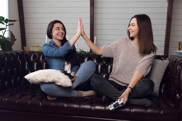Meisjes geven elkaar vijf, vrouwelijke gamers spelen de gameconsole en hebben plezier thuis. hoge kwaliteit foto