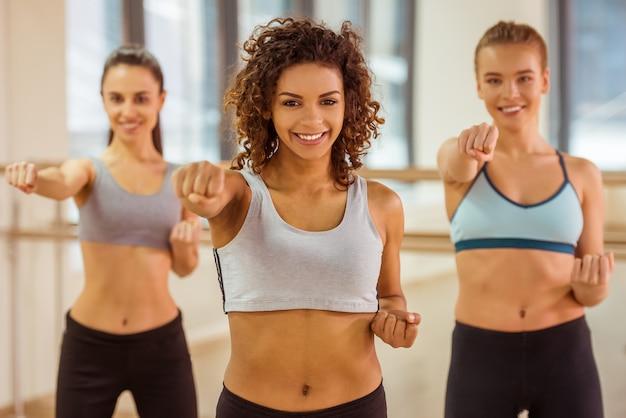 Meisjes glimlachen tijdens het sporten en het ontwikkelen van kracht.