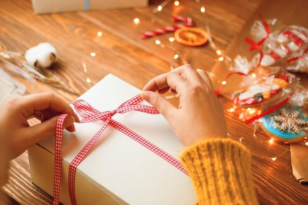 Meisjes handen in gebreide trui stropdas rood lint strik op witte geschenkdoos slinger lichten peperkoek en d...