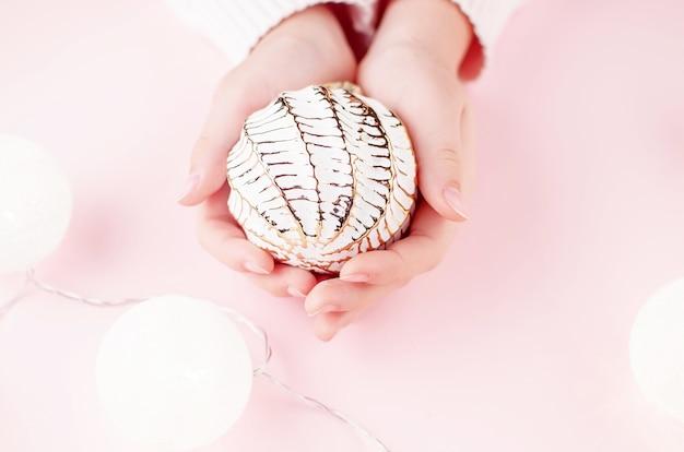 Meisjes handen met lichte garland op roze pastel achtergrond. kerst- en vakantieconcept,