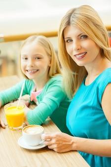 Meisjes hebben een pauze. vrolijke moeder en dochter ontspannen samen in café
