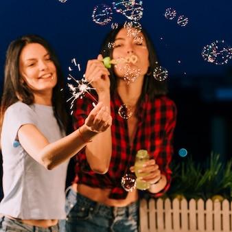 Meisjes hebben plezier met zeepbellen en vuurwerk