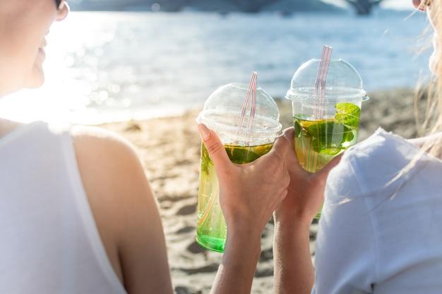 Meisjes houden mojito op het strand en gerinkelglazen