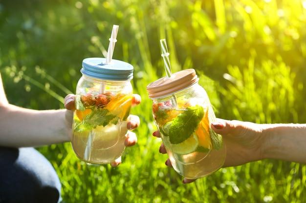 Meisjes houden verse limonade in potten met rietjes. hipster zomerdrankjes. milieuvriendelijk in de natuur. citroenen, sinaasappelen en bessen met munt in het glas. groen hoog gras buitenshuis.